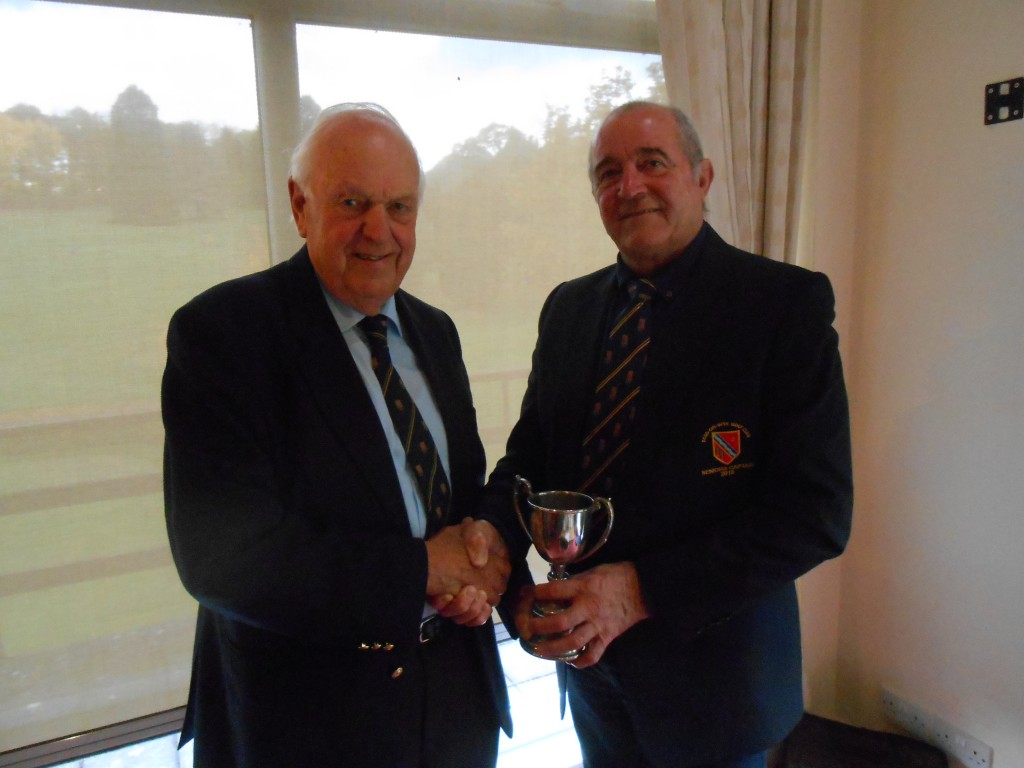 l to r, Club President Neville Ovens receiving the Annual Seniors Over 75's Cup from outgoing Seniors Captain Richard Topping.